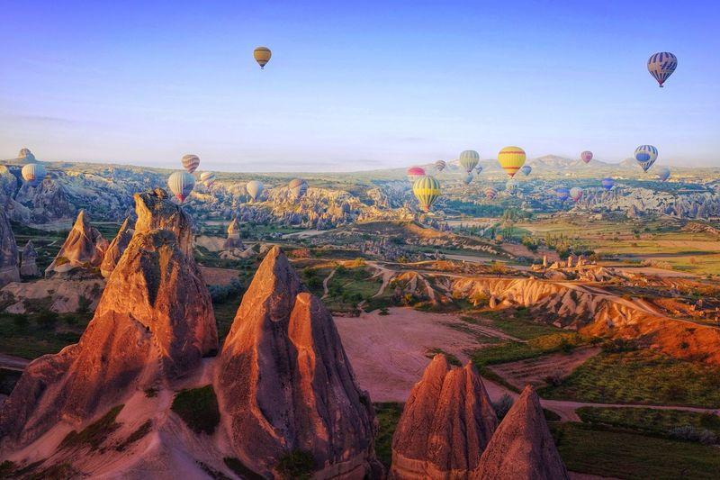 Hot air balloons flying over rock formations at cappadocia
