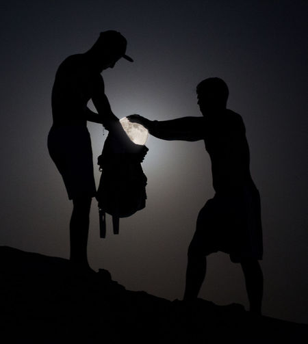 Optical illusion of silhouette men putting moon in bag
