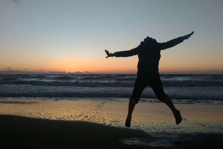 Silhouette man with arms raised on beach against sky during sunset