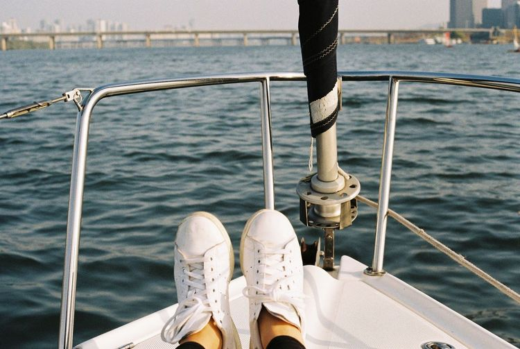 Low section of woman wearing white shoes sitting in boat on sea