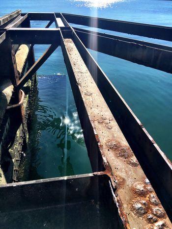 Metal beams extending out into the harbour Metal Metal Beams Rusty Harbour Water Sunlight