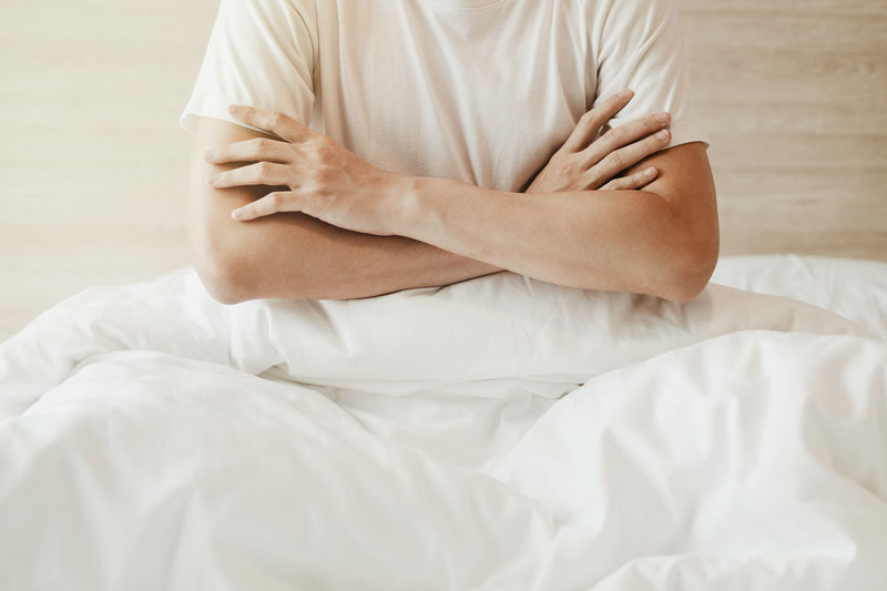Midsection of woman sitting on bed