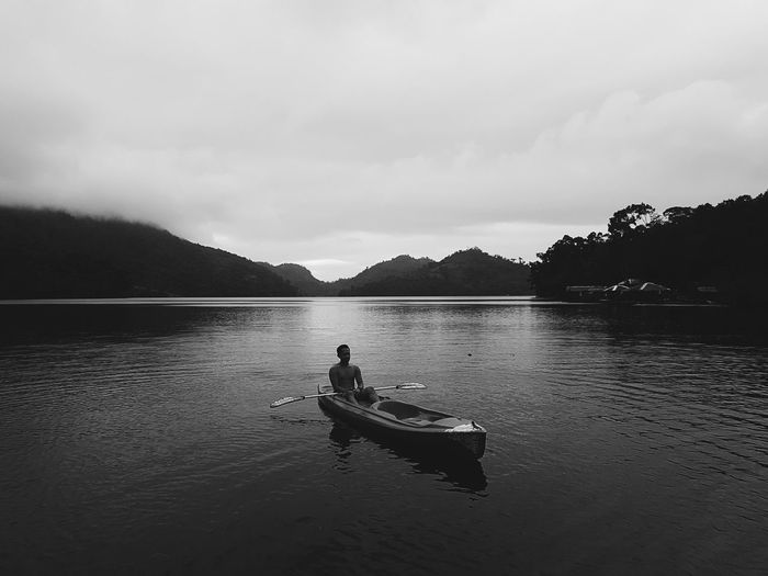 Man boating on lake against cloudy sky during sunset