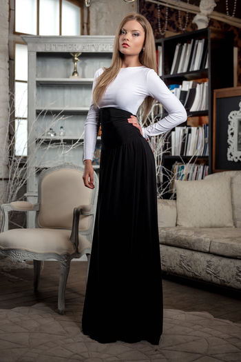Confident Woman Wearing Dress With Hand On Hip While Standing At Home