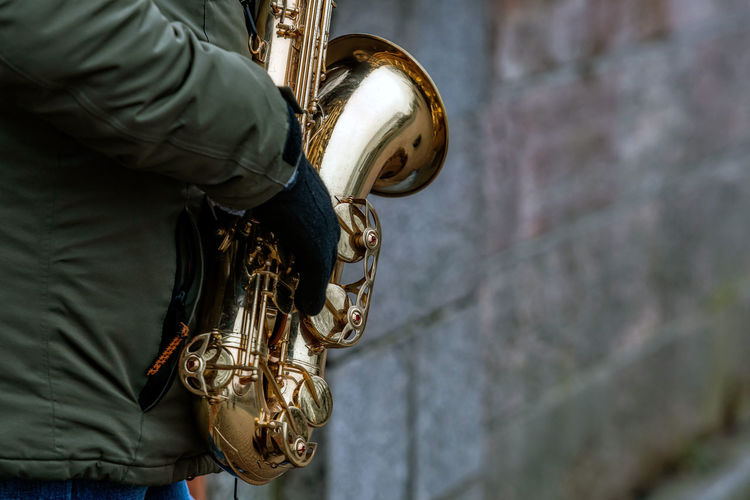 Midsection of man holding musical instrument while standing by wall