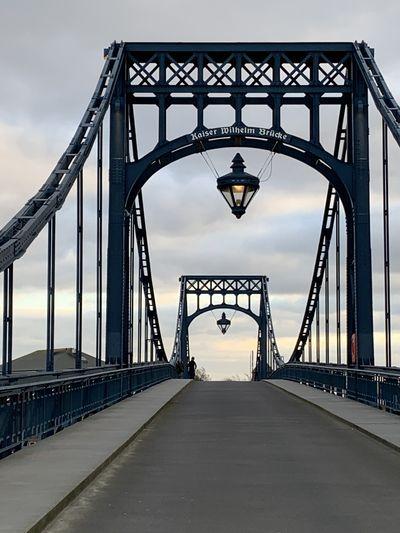 View of footbridge against cloudy sky