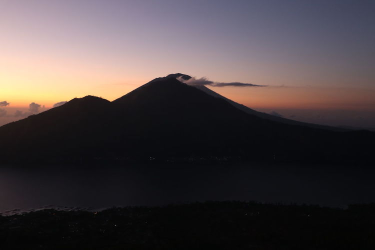 Scenic view of silhouette mountains against sky during sunrise on mount batur