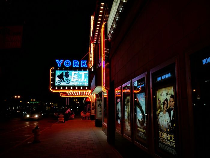 Exterior of illuminated movie theater by footpath at night