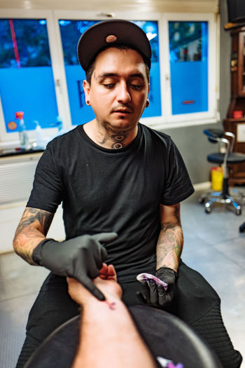 Blue Casual Clothing Colitis Crohns Crohnsdisease Focus On Foreground Front View Holding Leisure Activity Lifestyles Mid Adult Men Person Portrait Sitting Smart Phone Tattoo Tattooing Wireless Technology Worldibdday Young Men The Photojournalist - 2016 EyeEm Awards