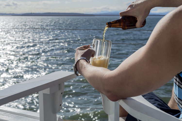 Man sitting by the sea pouring beer into mug Adirondack Chairs Adult Alcohol Ale Beer Beverage Cruise Day Deck Golden Human Element Lake Leasure Man Masculine Mug Mugs Outdoors Pouring Relaxing Sailing Sea Sitting Sunburst View