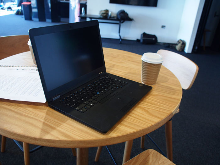 Casual office work space with laptop and coffee cup Caffiene,, Casual, Chair Close-up Coffee Cup Communication Day Desk Indoors  Keyboard Laptop No People Office, Table Technology Wireless Technology Wood - Material Work Space,