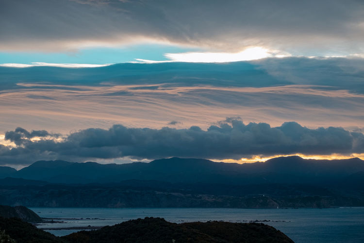 Scenic View Of Sea And Mountains Against Dramatic Sky