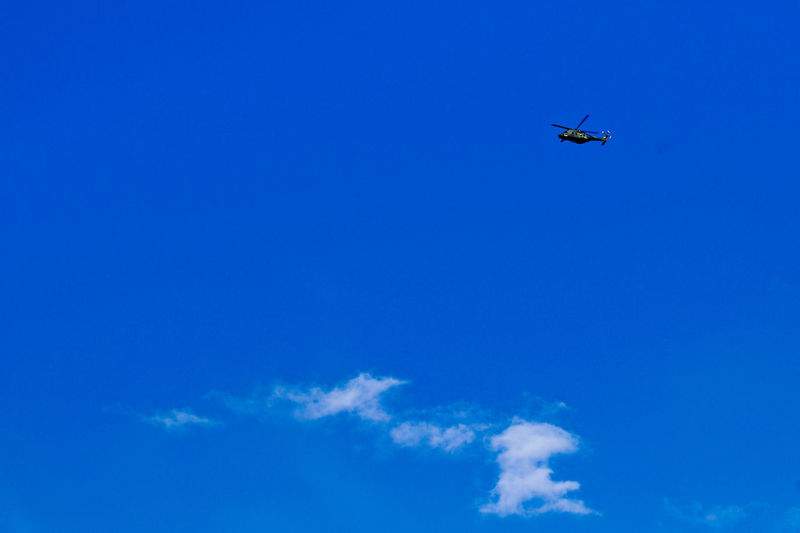 Low angle view of helicopter flying in sky