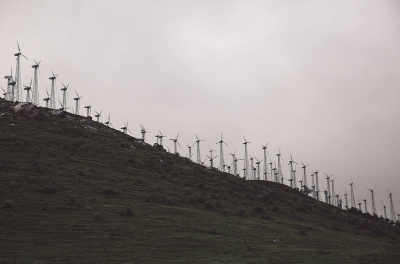 Low Angle View Of Wind Turbines On Hill