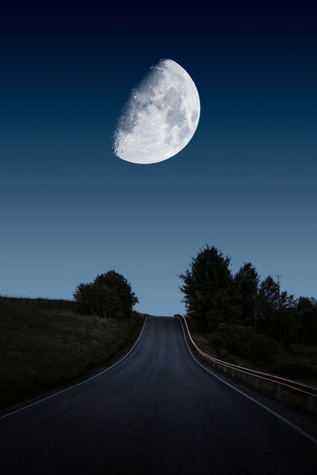 View of road against clear sky at night with huge moon