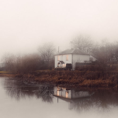 House by lake and buildings against sky during foggy weather