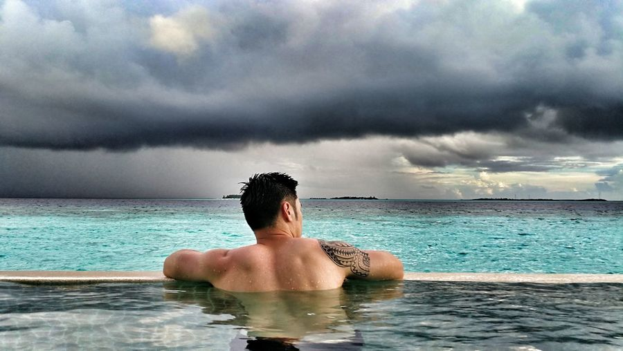 Rear view of man in infinity pool against cloudy sky