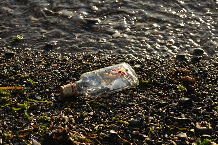 High angle view of garbage bottle on beach