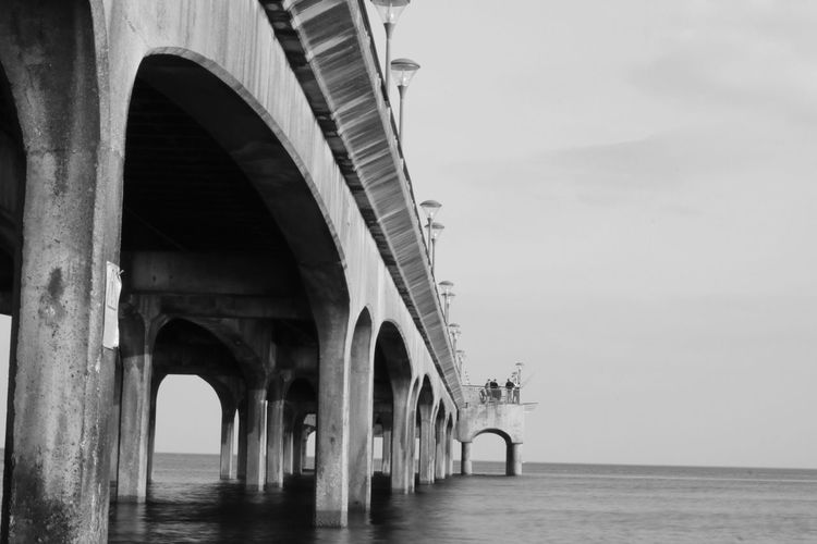 EyeEm Selects Architecture Built Structure Arch Water Sky Architectural Column Sea Day Bridge Connection Bridge - Man Made Structure Nature Transportation Building Exterior Real People Travel Incidental People Travel Destinations Waterfront Outdoors