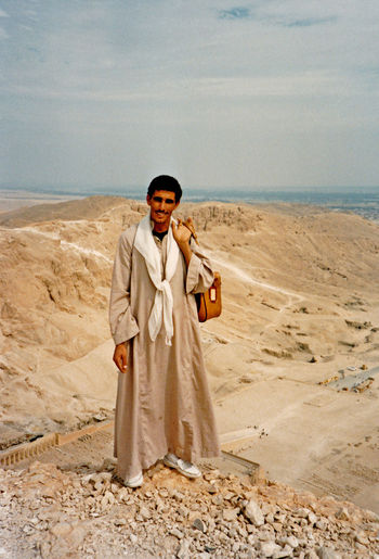 Local guide 'Abdul' stands on the cliff edge on the mountain path above the Valley of the Kings known locally as the Agatha Christie Path, Thebes, Luxor, Egypt. This mountain path, much used by Howard Carter, starts to the side of the rest house in the Valley and ends at Mortuary temple of Queen Hatshepsut in Deir El Bahari Desert People Sea Beach Nature Real People Sky Portrait Day Standing Outdoors Smiling Sand Valley Of The Kings Adult Holding Adults Only Front View Traditional Clothing Looking At Camera Young Adult Full Length One Person Young Men One Man Only Local Guide One Young Man Only Howard Carter Agatha Christie Path Standing On The Edge Of A Cliff Adventures In The City