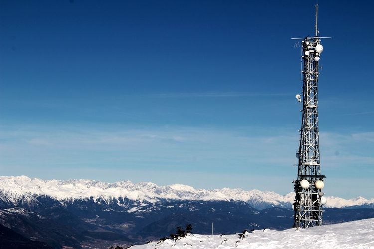 Communications tower against sky during winter