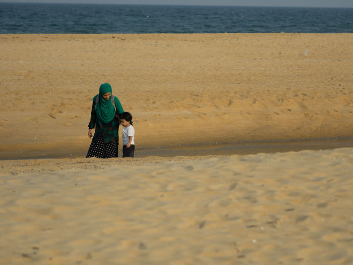 Mother and young boy walking on beach