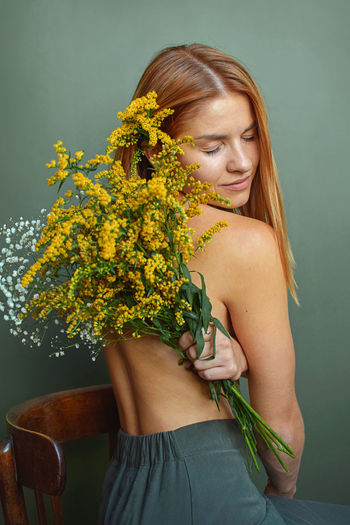 Midsection of woman standing by potted plant