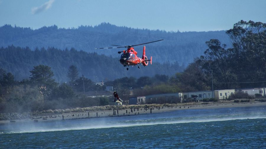 Coast guard training day Water Rescue Training Water Tree Nature Motion Real People Mid-air Sky Nature Flying Adventure Helicopter Air Vehicle Joy Extreme Sports Tree Exhilaration Transportation People Full Length Outdoors Day Sign