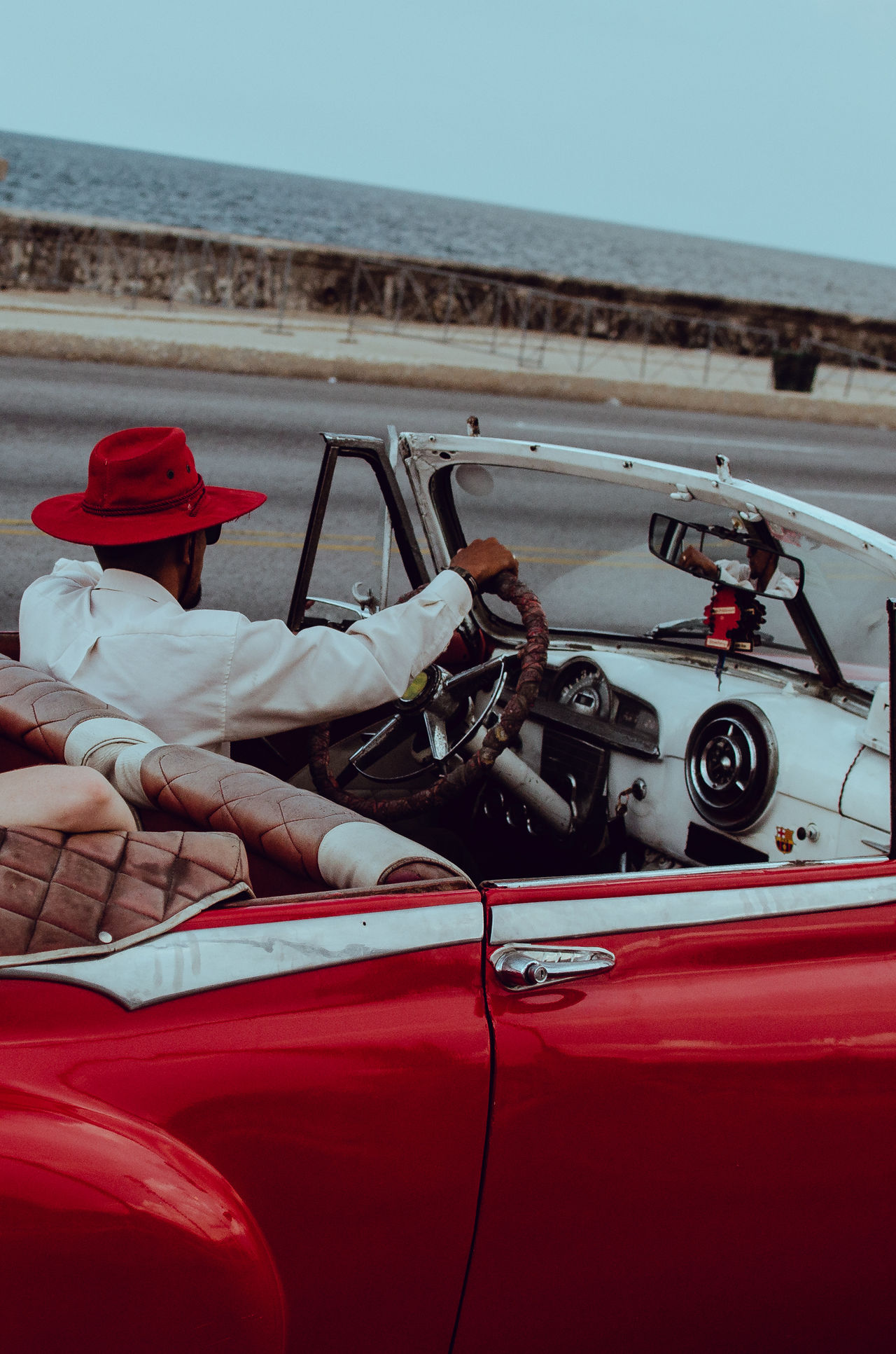 Man driving vintage car against sea