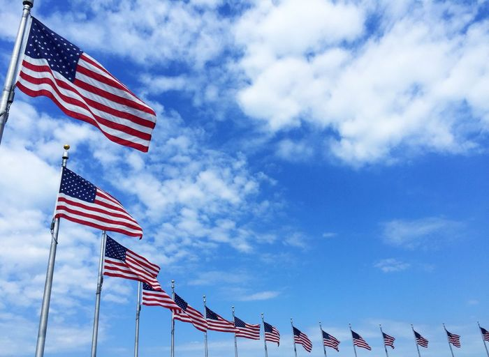 Low angle view of american flags around washington monument against sky