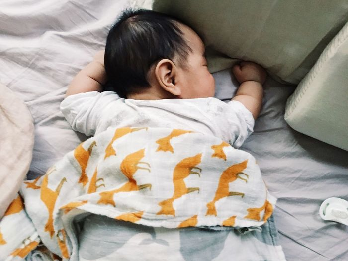 High angle view of baby girl sleeping on bed at home