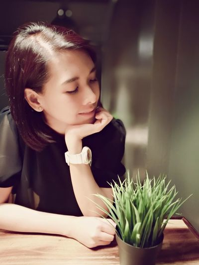 Beautiful Woman Looking At Houseplant On Table
