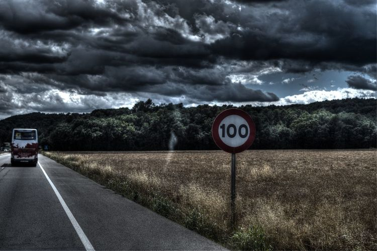 Road sign against cloudy sky