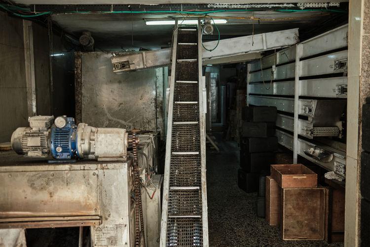 Interior of abandoned building old production workshop machine parts conveyor belt