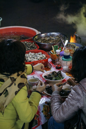 Rear view of people having food at night
