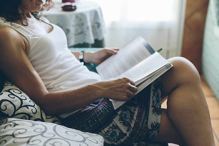 Midsection of woman reading book while sitting on sofa at home