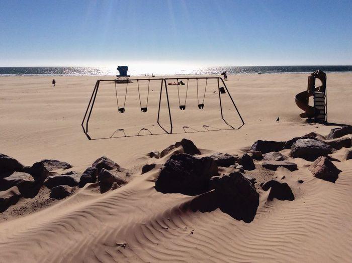 Swings And Slide On Beach Against Sky