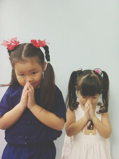 Cute Girls With Hands Clasped Praying While Standing Against Wall