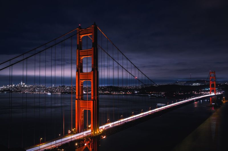 Golden gate bridge over bay against sky at night