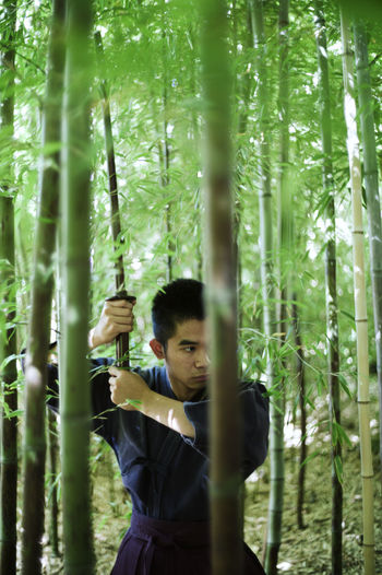 The modern samurai. Bamboo - Plant Bamboo Grove Beauty In Nature Day Forest Front View Green Color Growth Holding Leisure Activity Nature One Person Outdoors Real People Standing Tree Young Adult Young Women