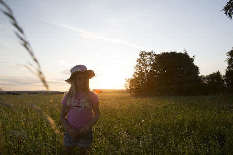 Cute girl standing amidst plants against sky during sunset