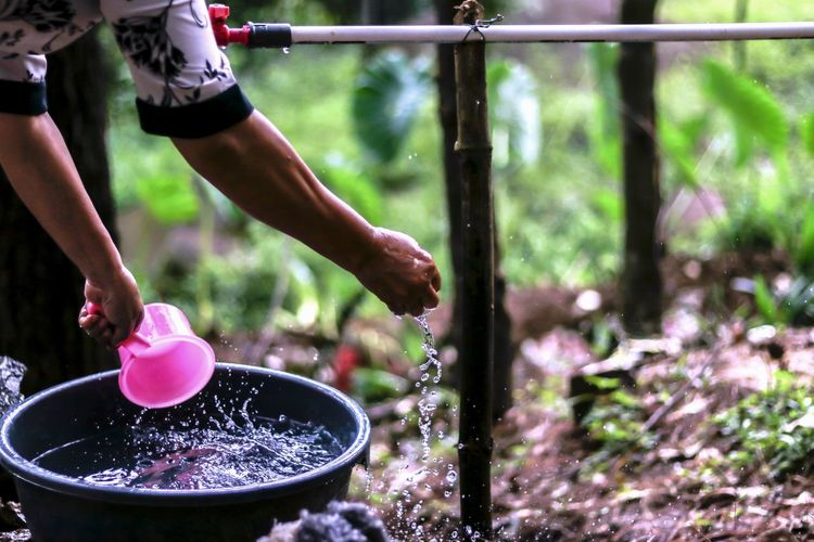 Cropped image of woman washing hands in yard