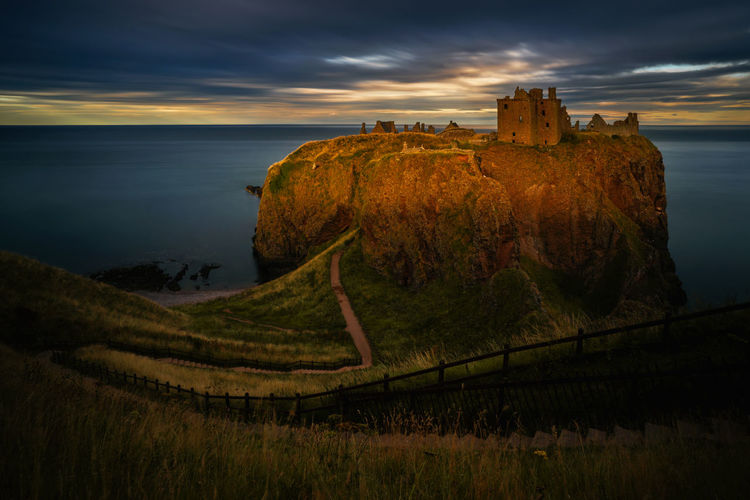 Dunnottar castle by sea against sky during sunset