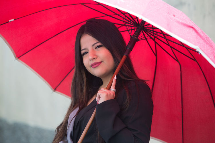 Portrait of beautiful young woman standing in rain