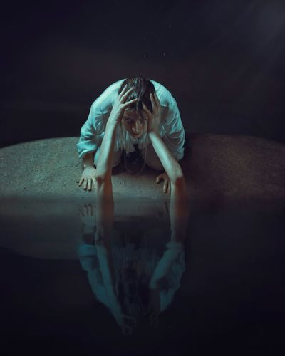 Cropped hand holding woman face through water in dark room