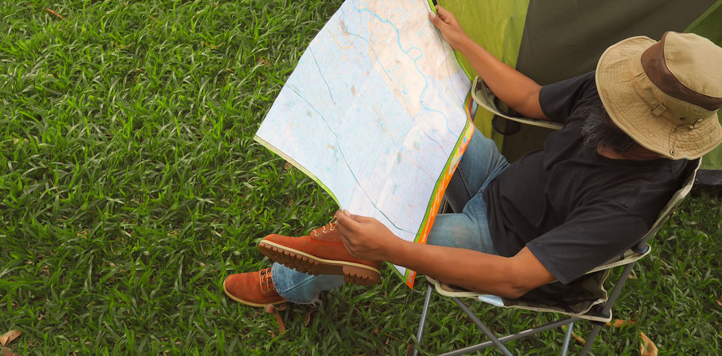 High angle view of man reading map while sitting on chair at campsite