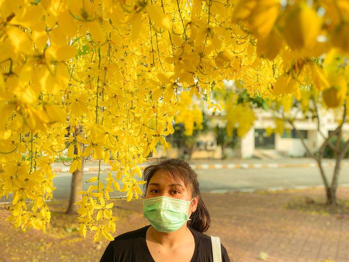Portrait of woman on yellow flowering plants