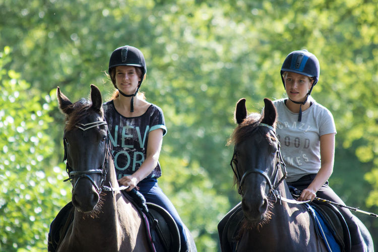 Teenagers riding horse against trees