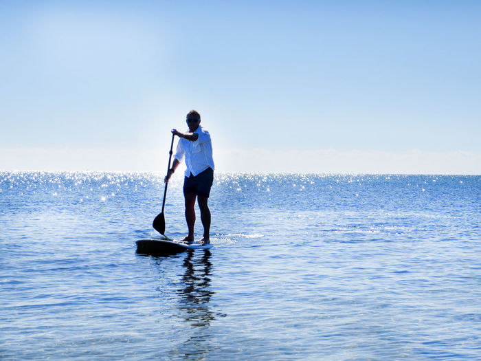 Carefree Escapism Getting Away From It All Leisure Activity Lifestyles Men Nautical Vessel Outdoors Paddle Boarding Real People Recreational Pursuit Rippled Sea Transportation Vacations Water Weekend Activities