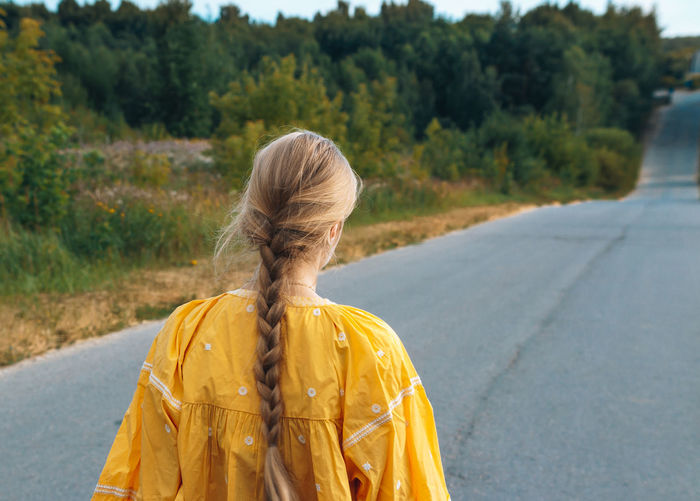 Rear view of woman standing on road against trees